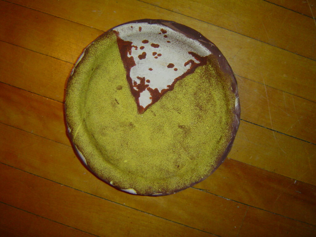 Photography on clay a pie plate made out of a photograph of a pie, with slice missing white plate, brown pie filling, yellow crust
