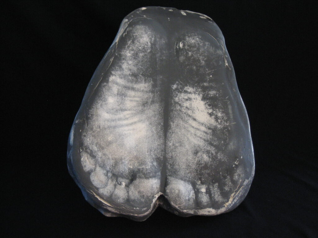 Feet, photograph on clay, gray scale, bottom of feet in detail