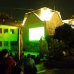 crowd in front of old building with projection on it