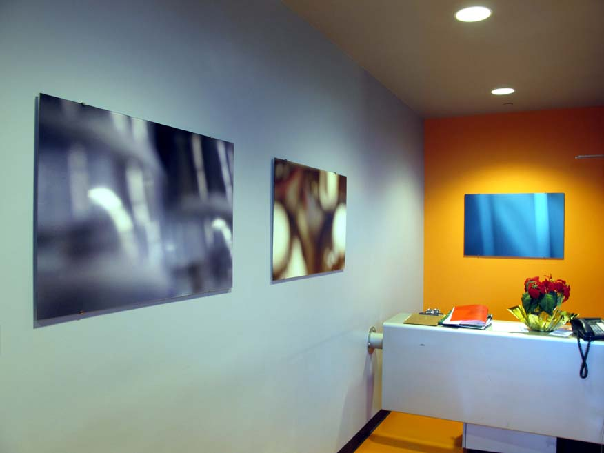 3 abstract photographs hanging on wall of office space