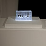 Glass block with letters mood in middle lit from underneath glows blue white light