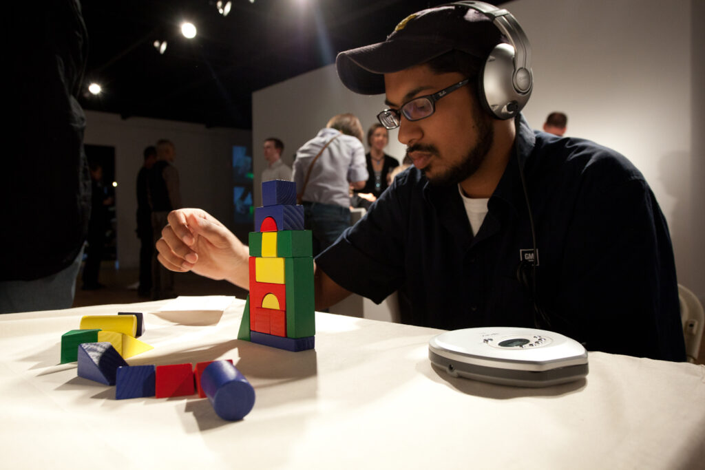 man sitting with headphones on building with multicolored blocks