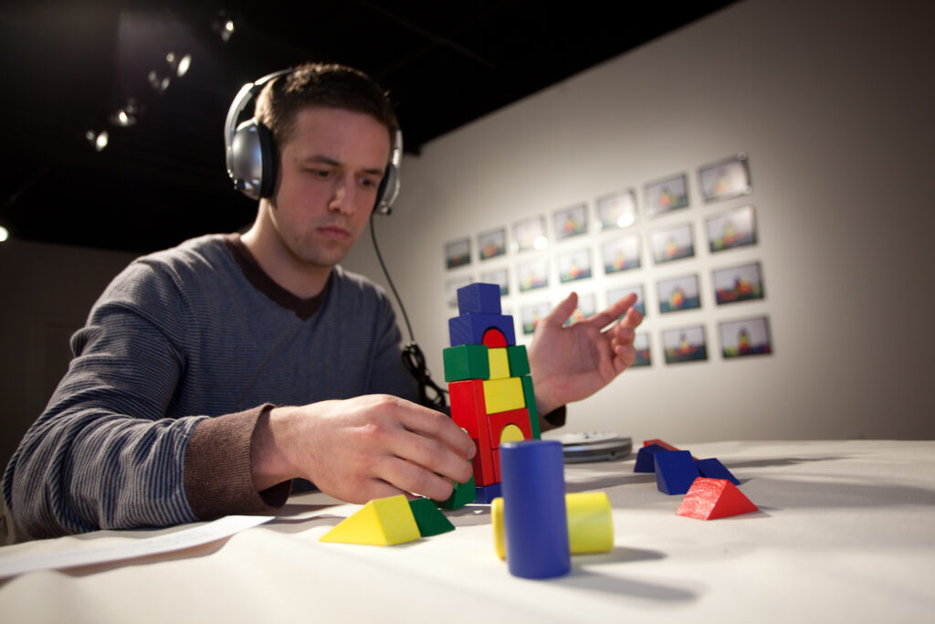 man sitting with headphones on building with multicolored blocks in front of a grid of photographs of buildings